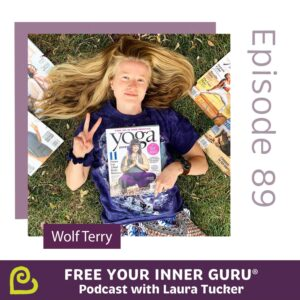 Photo of Wolf Terry lying on grass holding a Yoga Journal